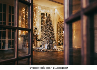 warm and cozy evening in Christmas room interior design,Xmas tree decorated by lights presents gifts,toys, deer,candles, lanterns, garland lighting indoors fireplace.holiday living room.magic New year