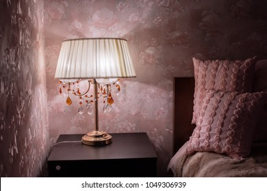 Warm cozy lamp near bed on night stand