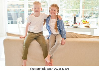 Warm and cozy portrait of two cute redhead kids, brother and sister, hugging each other and looking at camera  sitting on back of couch in living room at home with festive dinner table in background