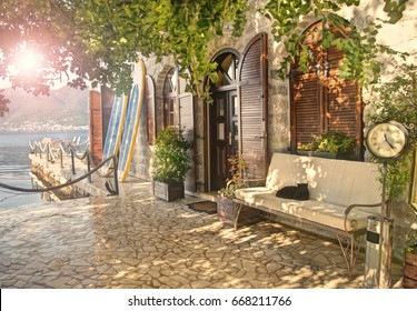 warm cross-processed image of sun shining through leaves of century old carob tree next to old house entrance with surf boards, bench, cat lying on it and clock  in Tivat at sunset, Montenegro