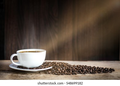 warm cup of coffee on brown background, morning sunset