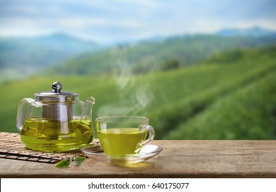 Warm cup of green tea and glass jars with organic green tea leaf on wooden table in the tea plantations background