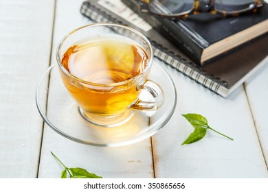Warm cup of tea and book on white wooden