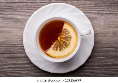 Warm cup of tea with lemon standing on wooden table.