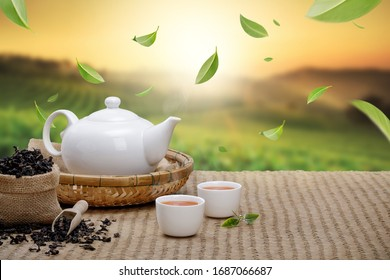 Warm cup of tea with teapot, flying green tea leaves in the air and dried herbs on the bamboo mat at morning in plantations background, Organic product from the nature for healthy with traditional