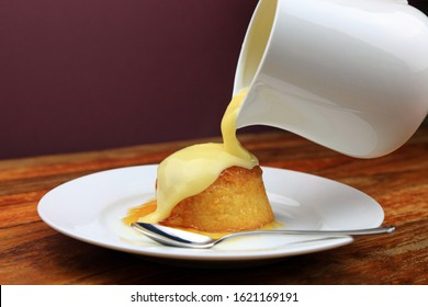 Warm Custard Being Poured From A Jug Over A Treacle Sponge Pudding.