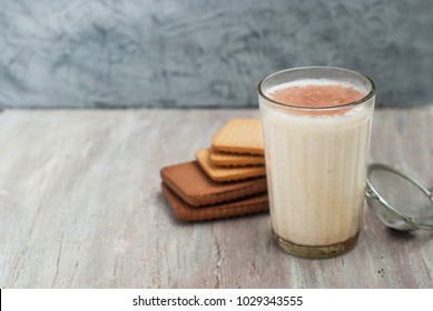 Warm Drink with Milk and cinnamon Powder on Silver Plate and Cocoa Biscuits on gray rustic Background. Horizontal image.