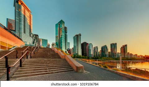 A warm evening with an emerald sky flooded with orange ocean in the city with modern glass skyscrapers and a stone staircase