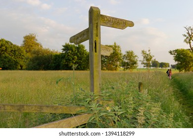 Warm evening sun shines on the fields trees and footpath sign behind Oakley village hampshire