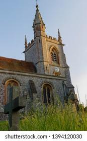 Warm evening sun shines on St Leonard's Church in Oakley hampshire