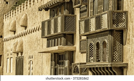 The warm exterior of a traditional house made of wood and plaster with a colour filter applied showing lattices made of wood covering windows. Taken at the Janadriyah Festival in Riyadh, Saudi Arabia.