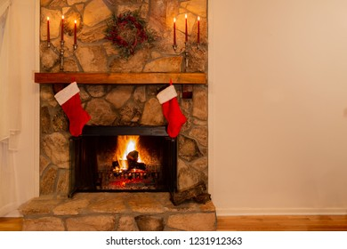 Warm fireplace with wreath, candelabras and two Christmas stockings in the family home.