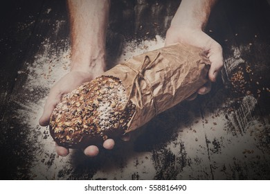 Warm fresh rye whole grain bread, wrapped in craft paper. Healthy baking and cooking concept background. Hands hold loaf on wooden table background, sprinkled with flour. Soft toning, filtered