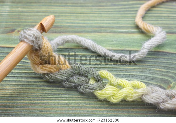 Warm green winter yarn ball for knitting and crochet on the wooden table. Closeup photo of crochet chain. Rustic crochet thread and a bamboo hook. Rustic background for creative craft work. Work place