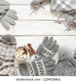 Warm grey woolen knitwear: socks, gloves, pom hat, scarf and cup of cocoa with marshmallow on white rustic wood background. Winter cozy still life.