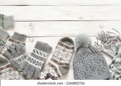Warm grey woolen knitwear: socks, gloves, pom hat and scarf on white rustic wood background. Winter cozy still life.
