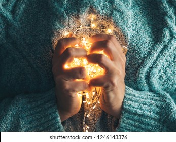 Warm heart, love concept. Women's hands holding a garland. Girl in a blue sweater with Christmas lights in her hands, warm Christmas mood, soft focus