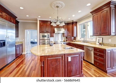 Warm and inviting kitchen with large kitchen island, cherrywood cabinets, gold granite counter tops and modern stainless steel refrigerator. Northwest, USA