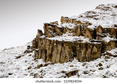 Warm and jagged rock face rising from the snow-covered hillside with a gray and obscure cloud-covered  sky