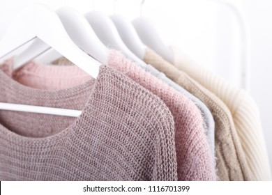 Warm knitted, autumn, winter clothes hanging on a rack, trending concept,pastel colors