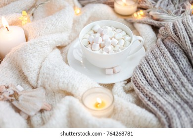 Warm knitted blanket, cup of coffee, marshmallows, christmas lights, vintage toy, candles
