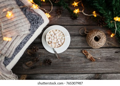 Warm knitted blanket, cup of coffee with marshmallows, Christmas lights on a wooden table