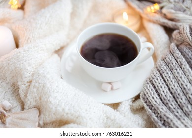 Warm knitted blanket, cup of hot coffe, christmas lights, vintage toy, candles
