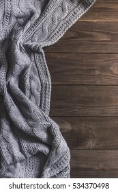 Warm Knitted crumpled gray blanket on a wooden background. Top view, space for text