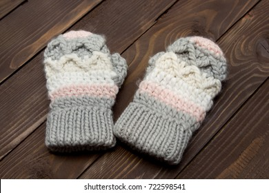 Warm knitted gloves on wooden background. Clothes for winter.