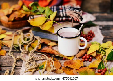 Warm knitted scarf and a book on a wooden tray. Peaceful Fall Fruit, Leaf, Acorn Still Life on Rustic . autumn still life with a cup of tea. Cup of tea with autumn leaves reflection on book