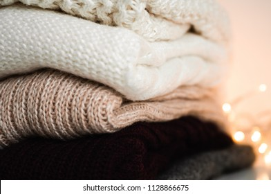 Warm knitted sweaters. Pile of knitted clothes on warm background, sweaters, knitwear, space for text, Autumn winter concept.