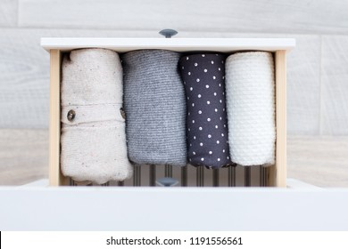 warm knitted woolen clothes, neatly folded into the chest of drawers