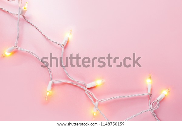 Warm  light garlands on pink background, festive decorations.  Flat lay, top view