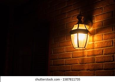 Warm light lantern illuminating the front porch at night - Shutterstock ID 1587811735