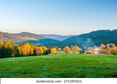 Warm light sunset panorama view of  Beskydy mountains with fog in the valley and blue cloudless sky, beutiful sunny afternoon in Czech mountains, Beskid Slaski near Lysa hora mountain.