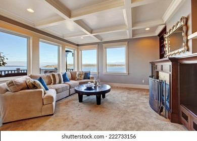 Warm living room interior with comfortable sofa, fireplace and coffee table. Room with coffered ceiling and soft brown carpet floor