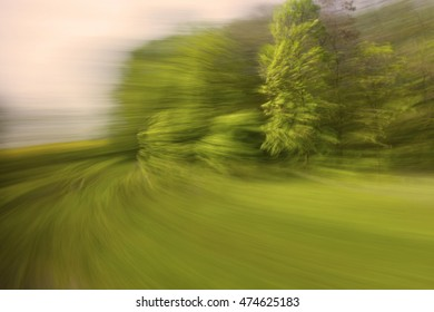 Warm looking motion blurred photographic background with trees and other vegetation against pink sky