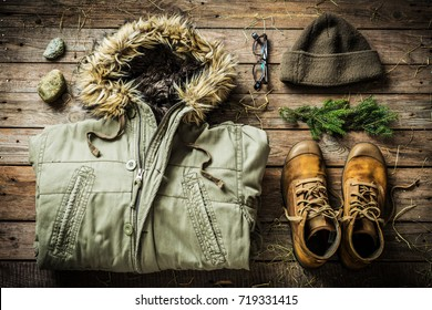 Warm male clothes (warm jacket, boots and hat). Winter or christmas weekend in country cottage (cabin) concept. Rustic cozy layout on wooden background captured from above (flat lay).