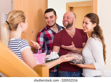 Warm meeting of happy friends holding gifts and sweets