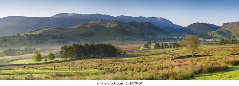 Warm misty morning light illuminating idyllic rural landscape of gently rolling hills, dry stone walls and pretty woodland, Lake District, Cumbria, UK.