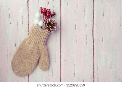 Warm mittens, cones and fir branches on a beautiful wooden pink background