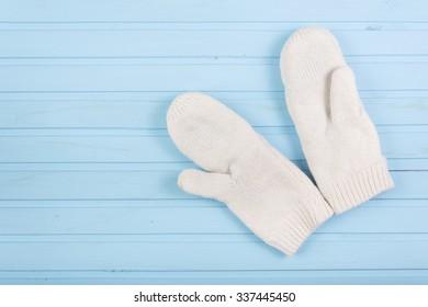 Warm mittens on blue wooden background