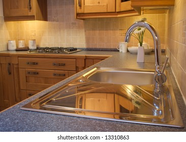 Warm Modern contemporary kitchen design tap, sink, worktop and cupboards in showroom