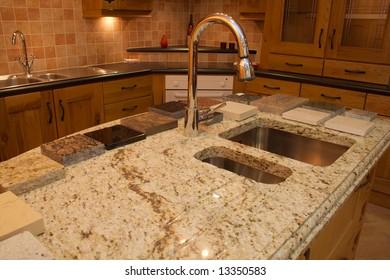 Warm Modern contemporary kitchen showing granite worktop  in showroom