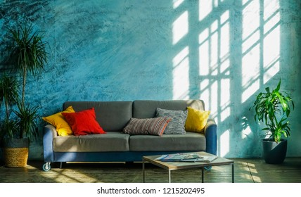 warm, modern living room, area in the early evening. light and shadows on blue wall. interior background. table with magazines, couch with pillows