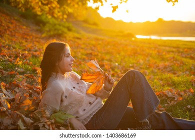 Warm moments of autumn. Woman pretty girl enjoy autumn. Girl relaxed lay fallen leaves on sunny autumn day. Warmth and coziness. Female autumn leaves background. Catching evening sunbeams.