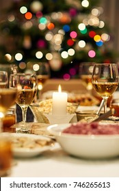 Warm mood around dining table full of a variety of delicious festive food and wine with a Christmas tree in the background