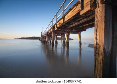 Warm morning light on the Granite Island Causeway, long exposure. Encounter Bay, Victor Harbor seaside holiday town, South Australia, Australia.
