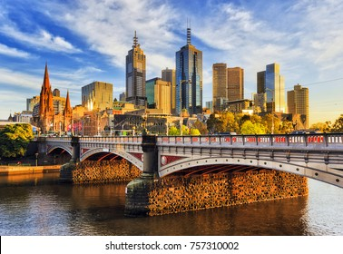 Warm morning light on high-rise towers in Melbourne CBD above Princes bridge across Yarra river.