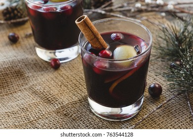 Warm Mulled Red Wine In A Glass With Fruit and Cinnamon Stick on Rustic Winter Table